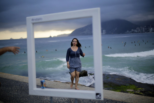 Tourists pose for photos in front of Brazil's famous Ipanema beach, Wednesday, June 11, 2014 in Rio de Janeiro, Brazil. (Photo by Wong Maye-E/AP Photo)