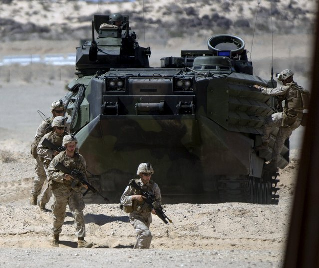 U.S. Marines from Fox Company, 2nd Battalion 1st Marines, 13th Marine Expeditionary Unit clear ahead of an Amphibious Assault Vehicle (AAV) during a non-live fire Military Operations in Urban Terrain (MOUT) training at US Marine Corps: Marines Air Ground Combat Center in Twentynine Palms, California September 1, 2015. (Photo by Mario Anzuoni/Reuters)