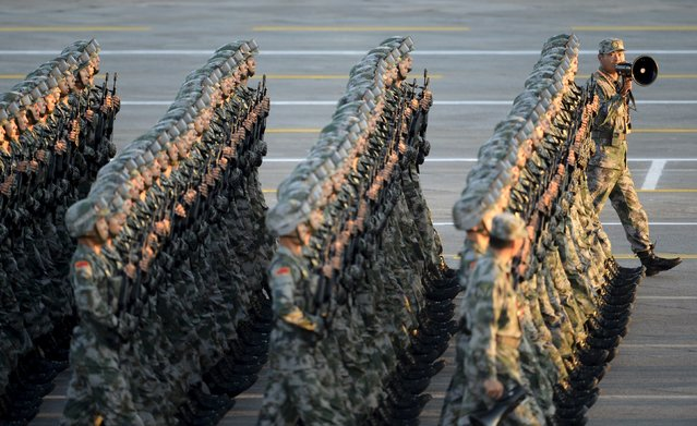 An officer (R) gives instructions as People's Liberation Army (PLA) soldiers march in formation on the Tiananmen Square during a rehearsal ahead of a military parade to mark the 70th anniversary of the end of World War Two, in Beijing, China, September 3, 2015. (Photo by Reuters/Stringer)