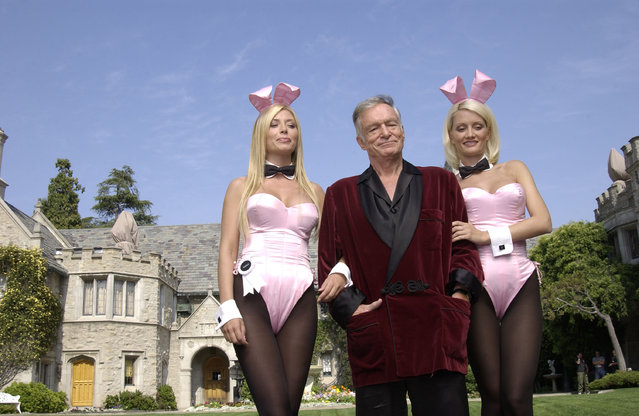 """(L to R) Playboy bunny Sheila Levell, Playboy founder Hugh Hefner and Playboy bunny Holly Madison perform a scene during the filming of a commercial for """"X Games IX"""" at the Playboy Mansion May 6, 2003 in Holmby Hills, California. This year's X Games will take place at STAPLES Center in Los Angeles from August 14th through 18th. (Photo by Robert Mora/Getty Images)"""