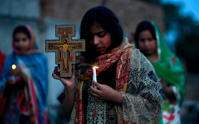 Christians hold candles as they offer prayers during an Easter service in the rooftop of their house during a government-imposed nationwide lockdown as a preventive measure against the COVID-19 coronavirus, in Islamabad on April 12, 2020. (Photo by Aamir Qureshi/AFP Photo)
