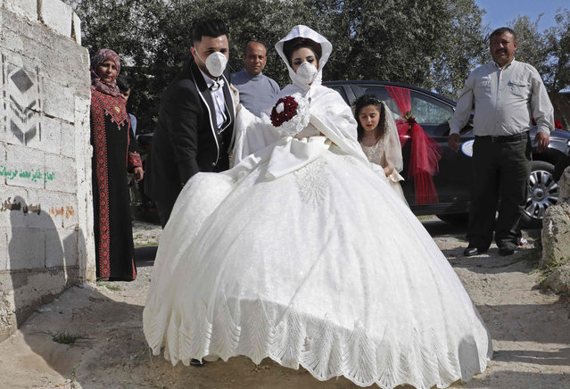 Newlywed Baraa (C) and Ammar arrive for their wedding ceremony at home in the West Bank village of Dora near Hebron on April 4, 2020, as authorities imposed restrictions on large gatherings in a bid to stem the spread of the COVID-19 coronavirus. (Photo by Hazem Bader/AFP Photo)