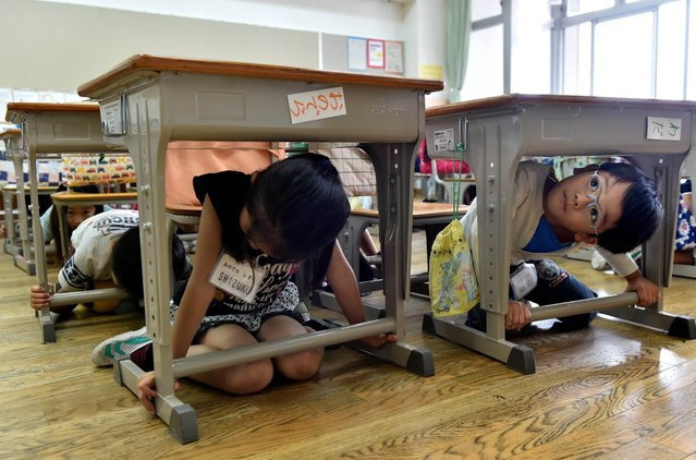 Elementary school children take cover under their desks during an earthquake drill at a school in Tokyo on September 1, 2014. Nationwide anti-disaster drills were held on September 1 on the anniversary of the massive 1923 earthquake which killed more than 140,000 people in the Tokyo metropolitan area. (Photo by Yoshikazu Tsuno/AFP Photo)