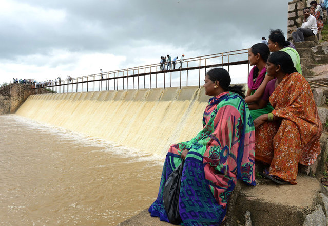 Indian villagers sit near the overflowing Laknapur Project irrigation channel following heavy rain in the Parigi Mandal are of Ranga Reddy District, some 80 kms from Hyderabad on September 1, 2014. Heavy rainfall in the area has affected infrastructure and forced residents to leave their homes and seek refuge in shelters. (Photo by Noah Seelam/AFP Photo)