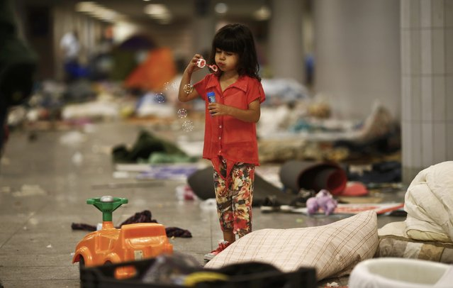 A girl makes soap bubbles in an underground station at the Keleti trainstation in Budapest, Hungary, September 4, 2015. (Photo by Bernadett Szabo/Reuters)