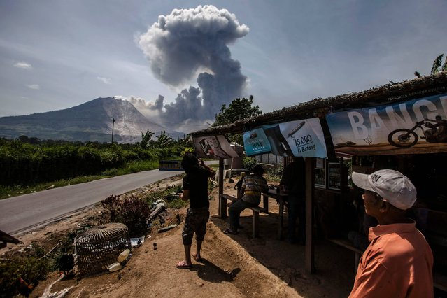 Indonesian residents look at the Mount Sinabung volcano as it spews volcanic ash near the Tiga Pancur village in Karo, North Sumatra on August 3, 2016. Volcanic eruptions in Indonesia in recent days have forced the closure of two airports and disrupted some flights to the holiday island of Bali, officials said August 3. Mount Sinabung, a volcano on the western island of Sumatra which has been rumbling for some time, also erupted violently on August 2, although its ash clouds did not disrupt any flights. (Photo by Y.T. Haryono/AFP Photo)