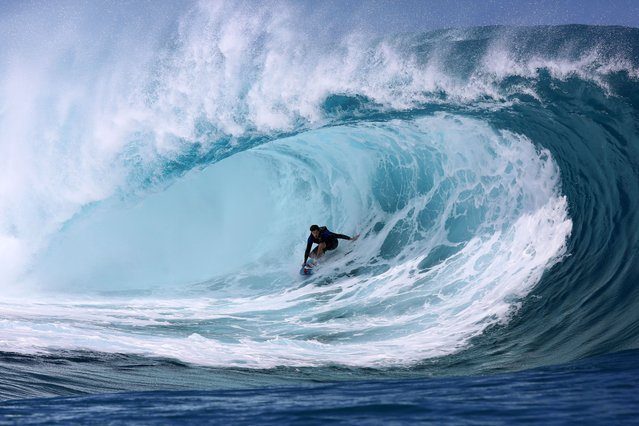 """A surfer rides a wave during the shooting of a remake of the 1991 classic """"Point Break"""" on September 11, 2014 in the Hava'e pass in Teahupoo, on the French Polynesian island of Tahiti. The American action thriller film directed by Ericson Core, starring Edgar Ramirez, Luke Bracey, Teresa Palmer and Ray Winstone, is a remake of the 1991 film then directed by Kathryn Bigelow. (Photo by Gregory Boissy/AFP Photo)"""