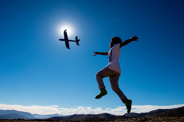 A boy plays with a toy plane on the eve of a solar eclipse, in La Higuera, Coquimbo Region, in the Atacama desert about 580 km north of Santiago, on July 1, 2019. A total solar eclipse will be visible from small parts of Chile and Argentina on July 2. (Photo by Martin Bernetti/AFP Photo)