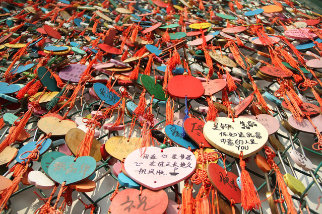 """View of a """"love confession"""" wall covered with lovelocks and heart-shaped wooden plates in Ji'nan city, east China's Shandong province on October 20, 2017. Lovelocks and heart-shaped wooden plates were hung on the """"love confession"""" wall in Jinan, capital of east China's Shandong province. The plates also contain information of those wanting to find a partner as November 11, known in China as """"Singles' Day"""", comes nearer. (Photo by Imaginechina/Rex Features/Shutterstock)"""