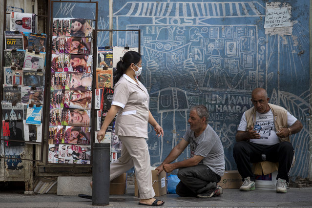 A maid from the Philippines wears a mask to help stop the spread of the new coronavirus as she walks in front of a newspaper kiosk in central Beirut's commercial Hamra Street, in Beirut, Lebanon, Wednesday, May 20, 2020. (Photo by Hassan Ammar/AP Photo)