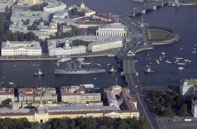 """An aerial view shows tug boats towing the """"Cruiser Aurora"""" along the Neva River in central part of St. Petersburg September 21, 2014. The former cruiser, which was used during the Russian-Japanese War in 1904-05 and the October Revolution in Russia in 1917, is towed for planned repair works, according to local media. (Photo by Reuters/Stringer)"""