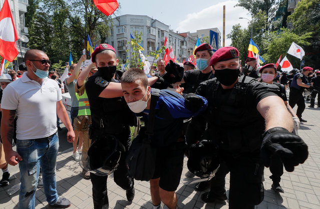 Ukrainian police officers detain a far-right militant who had previously allegedly attacked members and supporters of the Party of Shariy taking part in a protest rally in front of the Presidential Office in Kiev, Ukraine, 17 June 2020. (Photo by Sergey Dolzhenko/EPA/EFE)