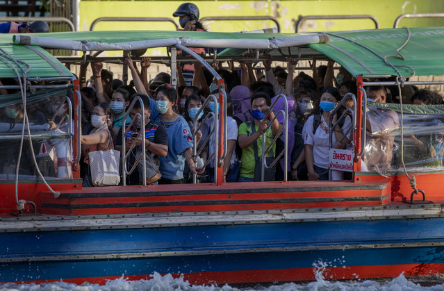 Passengers wearing face masks stand in close proximity as they ride a canal boat during the evening rush hour in Bangkok, Thailand, Wednesday, May 20, 2020. The Thai government continues to ease restrictions related to running businesses in the capital Bangkok that were imposed weeks ago to combat the spread of COVID-19. (Photo by Gemunu Amarasinghe/AP Photo)