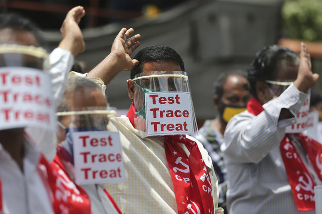 Activists of Communist Party of India Marxist display placards on face shields and shout slogans during a protest asking the state government to increase testing and free treatment for all COVID-19 patients in Hyderabad, India, Monday, June 29, 2020. Governments are stepping up testing and warily considering their next moves as the number of newly confirmed coronavirus cases surges in many countries. India reported more than 20,000 new infections on Monday. (Photo by Mahesh Kumar A./AP Photo)