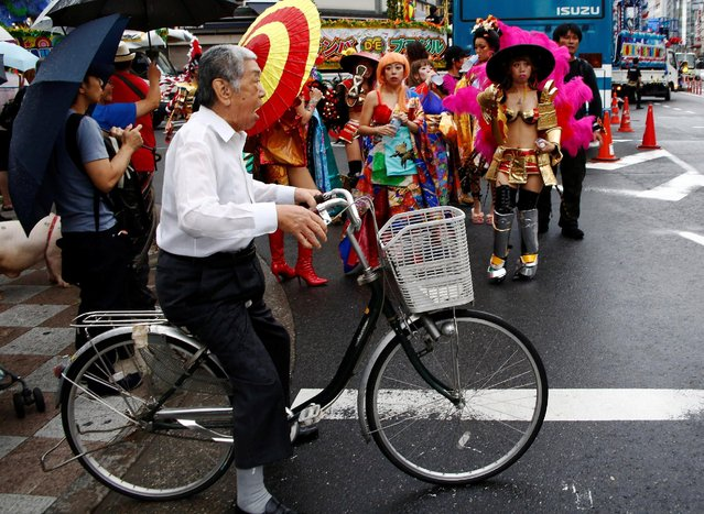 A man on a bicycle stands in front of Samba dancers after the annual Asakusa Samba Carnival in Tokyo, Japan August 27, 2016. (Photo by Kim Kyung-Hoon/Reuters)