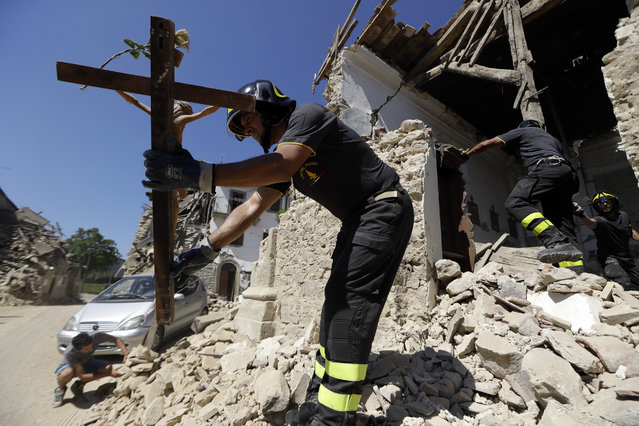 Firefighters retrieve a crucifix from a church in the small town of Rio, near Amatrice, central Italy, Sunday, August 28, 2016. Bulldozers with huge claws pulled down dangerously overhanging ledges Sunday in Italy's quake-devastated town of Amatrice as investigators worked to figure out if negligence or fraud in building codes had added to the quake's high death toll. (Photo by Andrew Medichini/AP Photo)