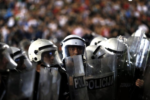 Serbian riot police officers secure the pitch during the Euro 2016 Group I qualifying match between Serbia and Albania at the Partizan stadium in Belgrade, Serbia, Tuesday, October 14, 2014. The European Championship qualifier between Serbia and Albania was suspended on Tuesday after pitch skirmishes involving players and fans over an Albanian flag that was flown above the stadium by a drone. (Photo by Marko Drobnjakovic/AP Photo)