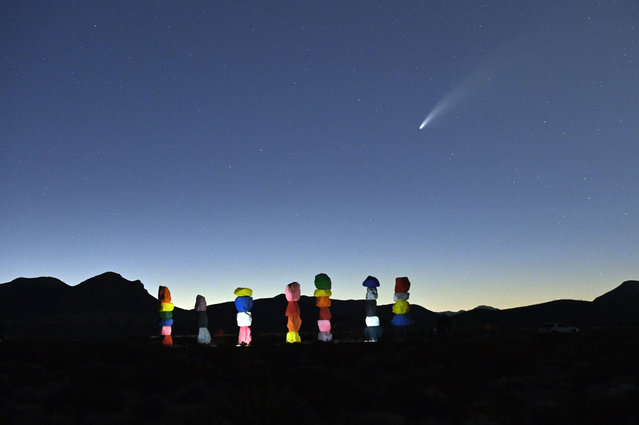 """Comet NEOWISE or C/2020 F3 is seen in the sky, above the """"Seven Magic Mountains"""" art installation by artist Ugo Rondinone, in Jean, Nevada on July 15, 2020. The comet was discovered March 27, 2020, by NEOWISE, the Near Earth Object Wide-field Infrared Survey Explorer, which is a space telescope launched by NASA in 2009. The """"Seven Magic Mountains"""" public art installation by artist Ugo Rondinone is located in the desert south of Las Vegas and is made up of seven pillars of colored boulders stacked more than 30 feet high. (Photo by David Becker/AFP Photo)"""