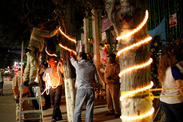 Municipal employees decorate a tree in preparation for an outdoor mass in memory of late iconic Mexican singer Juan Gabriel, outside his house in Ciudad Juarez, Mexico, September 1, 2016. (Photo by Jose Luis Gonzalez/Reuters)