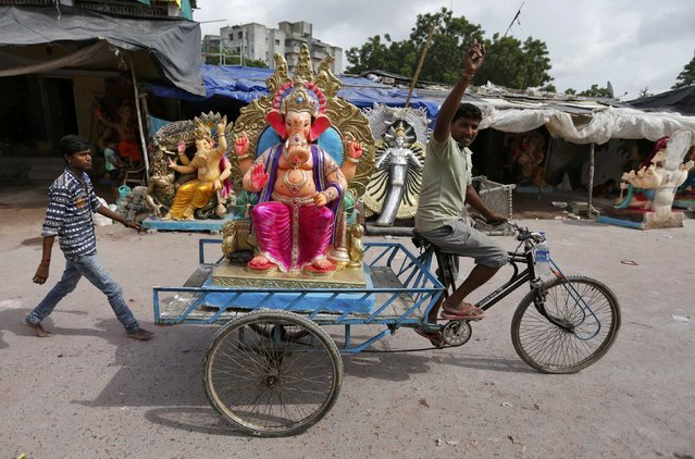 An idol of the Hindu god Ganesh, the deity of prosperity, is transported to a place of worship on the first day of the Ganesh Chaturthi festival in Ahmedabad, India, September 5, 2016. (Photo by Amit Dave/Reuters)
