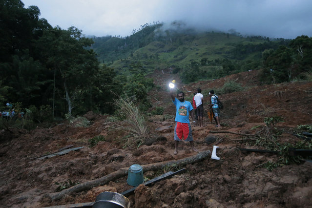 A man shines a torch as dusk falls at the site of a mudslide at the Koslanda tea plantation in Badulla district, about 220 kilometers (140 miles) east of Colombo, Wednesday, October 29, 2014. The mudslide triggered by monsoon rains buried scores of workers' houses at the tea plantation, killing at least 10 people and leaving more than 250 missing, an official said. (Photo by Eranga Jayawardena/AP Photo)
