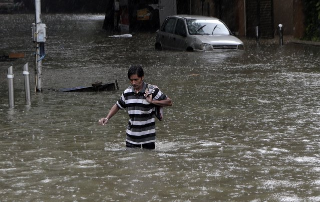 A man wades through a water logged street during heavy rain in Mumbai, India, Tuesday, August 4, 2020. India's monsoon season runs from June to September. (Photo by Rajanish Kakade/AP Photo)