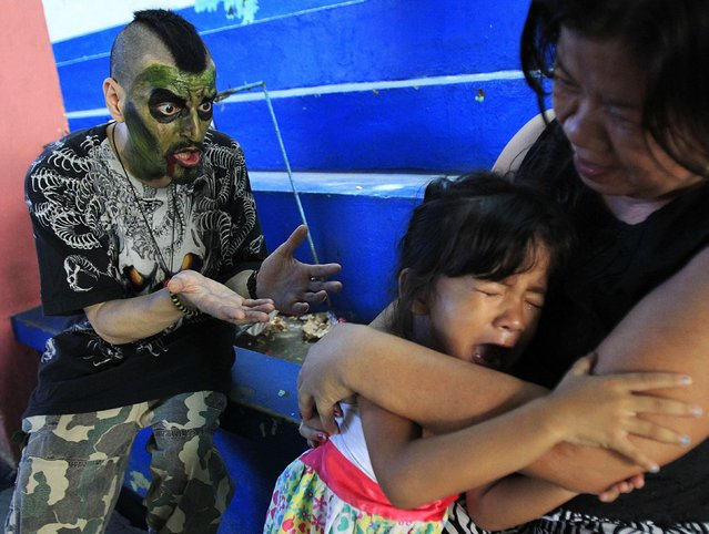 """A girl cries as a participant wearing zombie make-up approaches, after a """"Zombie Zumba Dance"""" event in Malabon city, north of Manila October 26, 2014. The city said the dance event, in conjunction with the Halloween season, is part of its promotion on healthy lifestyle. (Photo by Romeo Ranoco/Reuters)"""