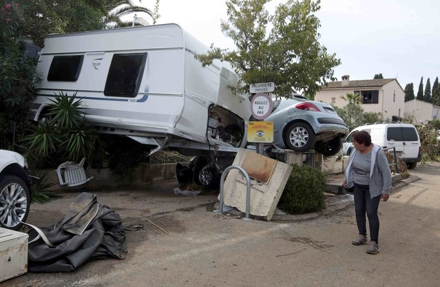 A woman walks near cars and caravan that were damaged after flooding caused by torrential rain in Biot, France, October 4, 2015. (Photo by Eric Gaillard/Reuters)
