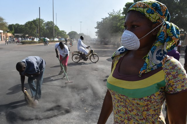 Inhabitants of Ouagadougou clean up the city on November 1, 2014. Rival military factions laid claim to power in Burkina Faso on Saturday after the west African nation's president fled following days of violent unrest over plans to extend his 27-year rule. (Photo by Issouf Sanogo/AFP Photo)