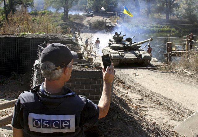 A member of the Organization for Security and Co-operation in Europe (OSCE) monitors the withdrawal of tanks of the Ukrainian armed forces near the village of Nyzhnje in Luhansk region, Ukraine, October 5, 2015. Ukraine has started withdrawing tanks and light artillery from the frontline in the eastern region of Luhansk in accordance with a recent agreement with pro-Russian separatists, the Ukrainian military said on Monday. (Photo by Reuters/Stringer)