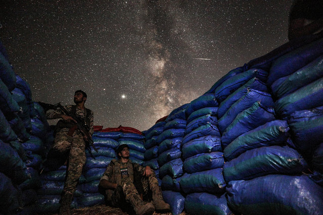 This long-exposure picture taken early on July 23, 2020, shows the Milky Way galaxy rising in the sky above Syrian fighters of the Turkish-backed National Front for Liberation group while on watch duty between sandbags in the town of Taftanaz along the frontlines in the country's rebel-held northwestern Idlib province. (Photo by Omar Haj Kadour/AFP Photo)