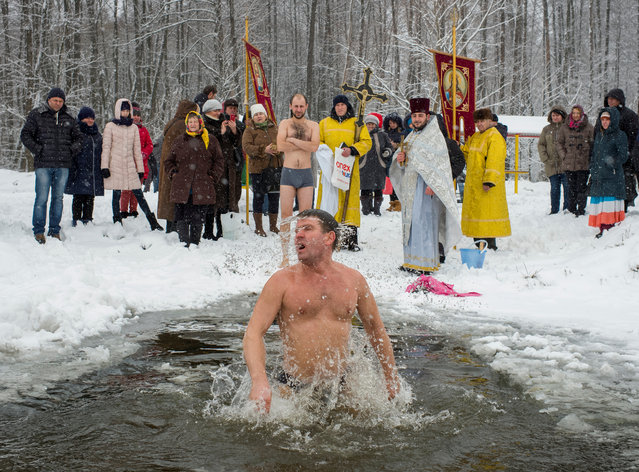 A man takes a dip in icy water during Orthodox Epiphany celebrations in the village of Ivankovychi, Ukraine on January 19, 2018. (Photo by Gleb Garanich/Reuters)