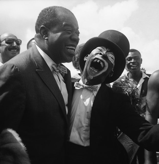 Louis Armstrong, noted jazz musician, gets a wide open greeting from Ajax Bukana, Ghana's leading jive dancer on arrival in Accra, Ghana on October 13, 1960. The top-hatted greeter was among a group which welcomed the visitor who is on a 35,000-mile concert tour of Africa. Armstrong and his band arrived in Lagos on October 18, and was given a boisterous welcome. (Photo by AP Photo)