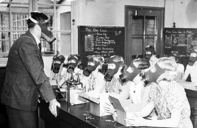 A teacher instructs his class in the correct gas mask drill in a school in Yorkshire, England, on September 15, 1939. (Photo by AP Photo)