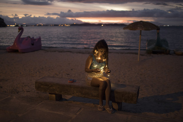 A reveler wearing lights sits on a bench during the dusk as she takes part in the Perola da Guanabara street party at Paqueta island in Guanabara Bay in Rio de Janeiro, Brazil, Saturday, February 3, 2018. (Photo by Leo Correa/AP Photo)