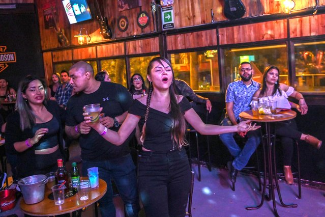 A woman sings as a band performs at a bar in Medellin, Colombia on September 19, 2020, amid the Covid-19 pandemic. Medellin left behind its strict quarantine and began to ease restrictive measures against the new coronavirus, mainly aimed at relaunching the commerce. (Photo by Joaquin Sarmiento/AFP Photo)