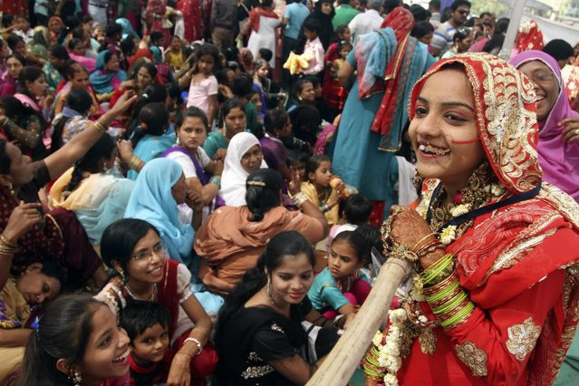 An Indian bride, right, interacts with a relative during a mass marriage of 162 Muslim couples in Ahmadabad, India, Sunday, March 3, 2013. Mass marriages in India are organized by social organizations primarily to help the economically backward families who cannot afford the high ceremony costs as well as the customary dowry and expensive gifts that are still prevalent in many communities. (Photo by Ajit Solanki/AP Photo/LaPresse)