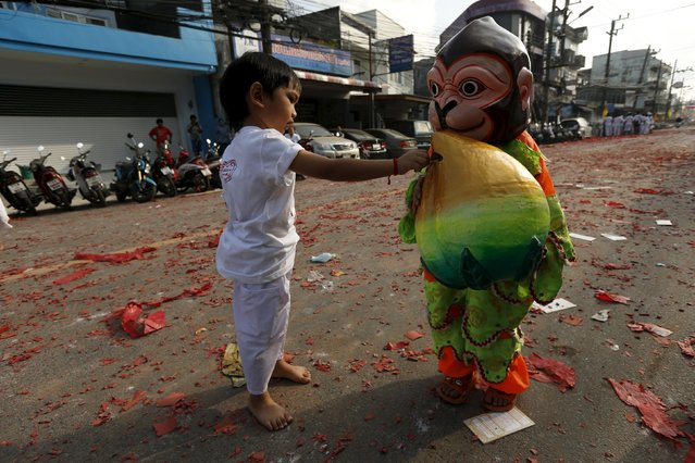 A boy gives money to another boy dressed as a monkey during Jui Tui shrine procession annual vegetarian festival in Phuket, Thailand October 19, 2015. (Photo by Jorge Silva/Reuters)