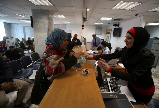 A Palestinian woman makes a withdrawal at the Housing Bank for Trade & Finance in the West Bank city of Ramallah January 22, 2013. (Photo by Mohamad Torokman/Reuters)