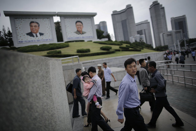 North Koreans walk in and out of an underpass leading to a subway station during morning rush hour while seen in the background are portraits of their late leaders Kim Il Sung, left, and Kim Jong Il on Wednesday, September 28, 2016, in Pyongyang, North Korea. (Photo by Wong Maye-E/AP Photo)