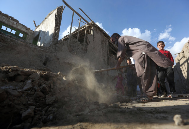 An Afghan man clears rubble from a damaged house following a strong earthquake, in Kabul, Afghanistan, Monday, October 26, 2015. The U.S. Geological Survey said the epicenter of the 7.5-magnitude earthquake was in the Hindu Kush mountains, in the sparsely populated province of Badakhshan, which borders Pakistan, Tajikistan and China. It said the epicenter was 213 kilometers (130 miles) deep and 73 kilometers (45 miles) south of the provincial capital, Fayzabad. (Photo by Rahmat Gul/AP Photo)