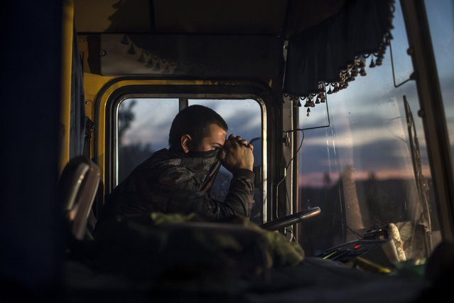 A driver sits inside a bus during an exchange of prisoners-of-war (POWs) near Donetsk, eastern Ukraine, in this September 21, 2014 file photo. (Photo by Marko Djurica/Reuters)