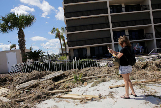 A woman takes pictures at debris and a damaged fence outside a building on the beach after Hurricane Matthew hit, in Jacksonville Beach, Florida, U.S., October 8, 2016. (Photo by Henry Romero/Reuters)
