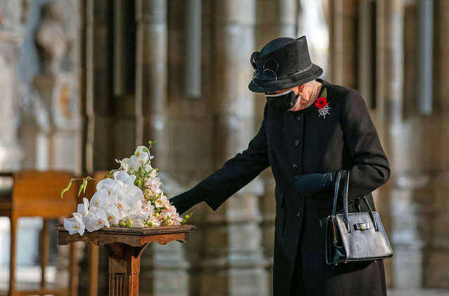 Queen Elizabeth inspects a bouquet of flowers to be placed at the grave of the Unknown Warrior by her Equerry, Lieutenant Colonel Nana Kofi Twumasi-Ankrah, during a ceremony in London's Westminster Abbey to mark the centenary of the burial of the Unknown Warrior, in Britain November 4, 2020. (Photo by Aaron Chown/Pool via Reuters)