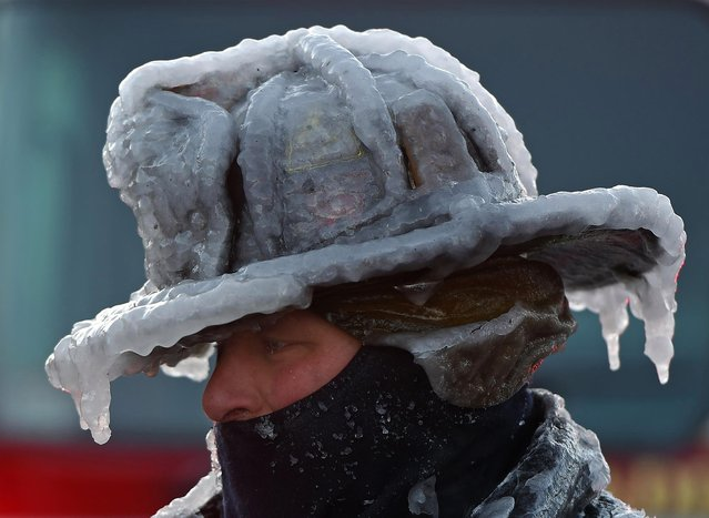 Firefighter Bobby Lehman, with his helmet and bunker gear caked in ice, tries to thaw out after battling a stubborn, wind-driven fire in Massachusetts, USA on January 4, 2018. (Photo by Polaris)