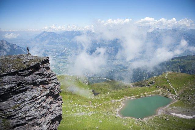 A hiker on a cliff edge looks down on the Baschalva lake in Wangs-Pizol, Switzerland, 16 July 2014. (Photo by Gian Ehrenzeller/EPA)