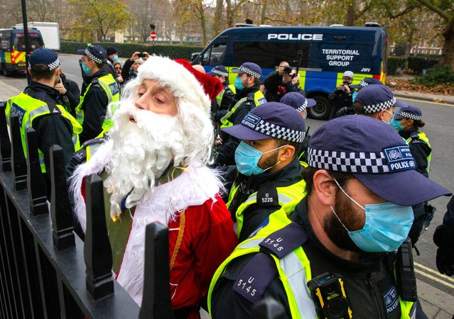 "An anti-lockdown activist dressed as Father Christmas is arrested in Grosvenor Square during a demonstration in London, England, on November 28, 2020. London is to return to ""Tier 2"" or ""high alert"" covid-19 restrictions once the current England-wide coronavirus lockdown ends next Wednesday. All three of the tiers, assigned to local authorities across England, have been strengthened since the lockdown began on November 5, however, with the main impacts to be felt by the hospitality sector. (Photo by Mark Thomas/i-Images)"