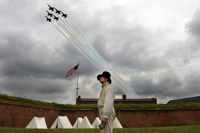 """Reenactor, Gary Schwartz of Silver Spring, MD stands near an encampment as the Blue Angels fly overhead during the Star-Spangled Spectacular Air Show which was part of the festivities celebrating the 200th Anniversary of the penning of """"The Star-Spangled Banner"""" and the Battle of Baltimore at Fort McHenry National Monument and Historic Shrine on Saturday September 13, 2014 in Baltimore, MD. (Photo by Matt McClain/The Washington Post)"""