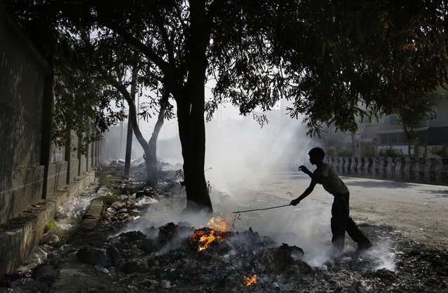 A young Indian ragpicker is silhouetted against smoke rising from the garbage burning on the roadside on the outskirts of New Delhi, India, Saturday, October 22, 2016. The Indian capital, laboring under the label of being the world's most polluted city, is trying something new to help clean up its air. A smartphone application that allows citizens to report the presence of construction dust or the burning of leaves and garbage in public parks to authorities was launched Friday. (Photo by Altaf Qadri/AP Photo)