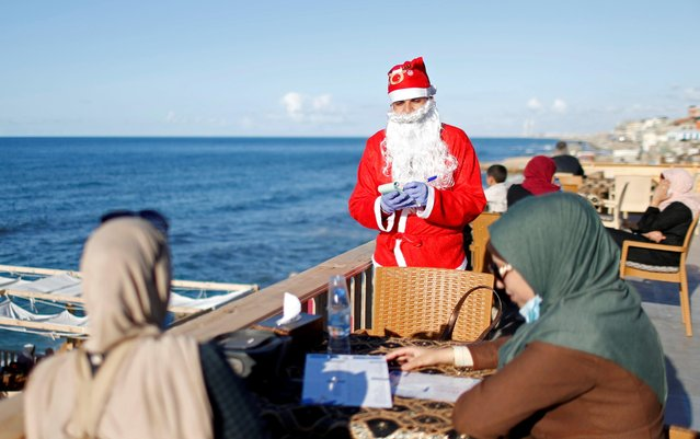 """A Palestinian waiter, dressed as Santa Claus, takes an order at """"Maldive Gaza"""" cafe on a beach in Gaza City, December 9, 2020. (Photo by Mohammed Salem/Reuters)"""